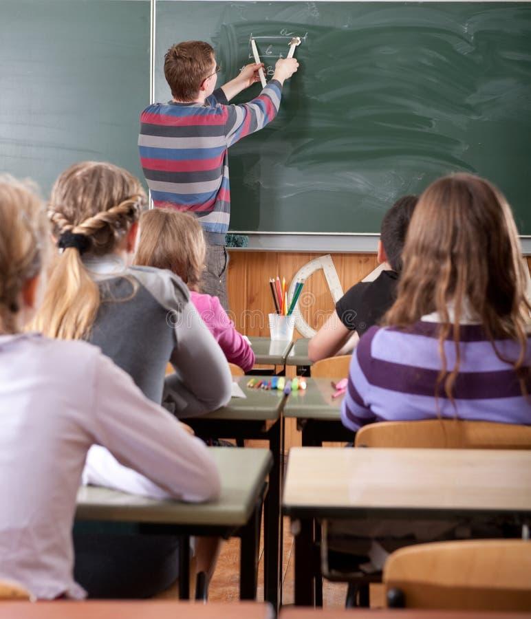 Junger männlicher Lehrer, der Mathe an der Tafel erklärt lizenzfreies stockfoto