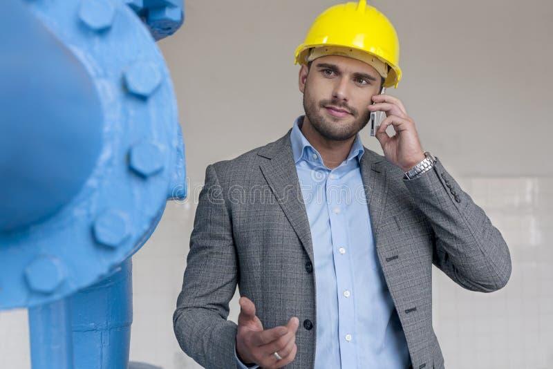 Junger männlicher Manager, der intelligentes Telefon in der Industrie verwendet lizenzfreie stockfotos