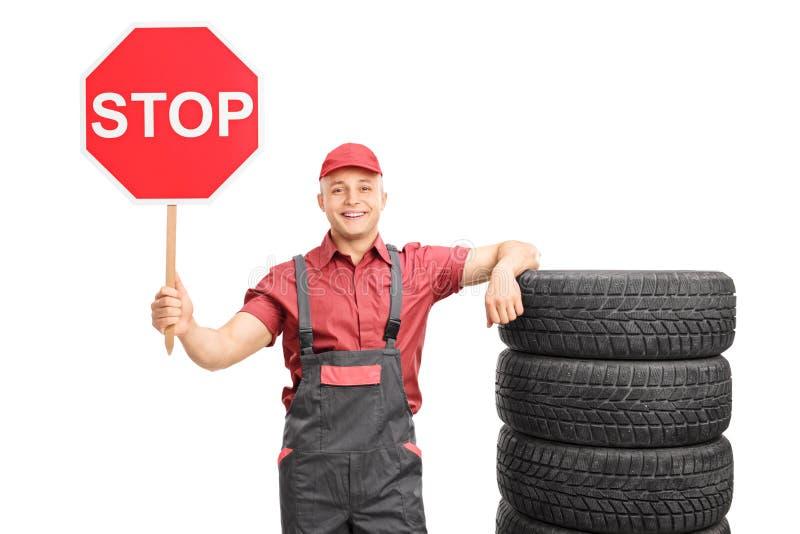Junger männlicher Mechaniker, der ein Stoppschild hält lizenzfreie stockfotografie