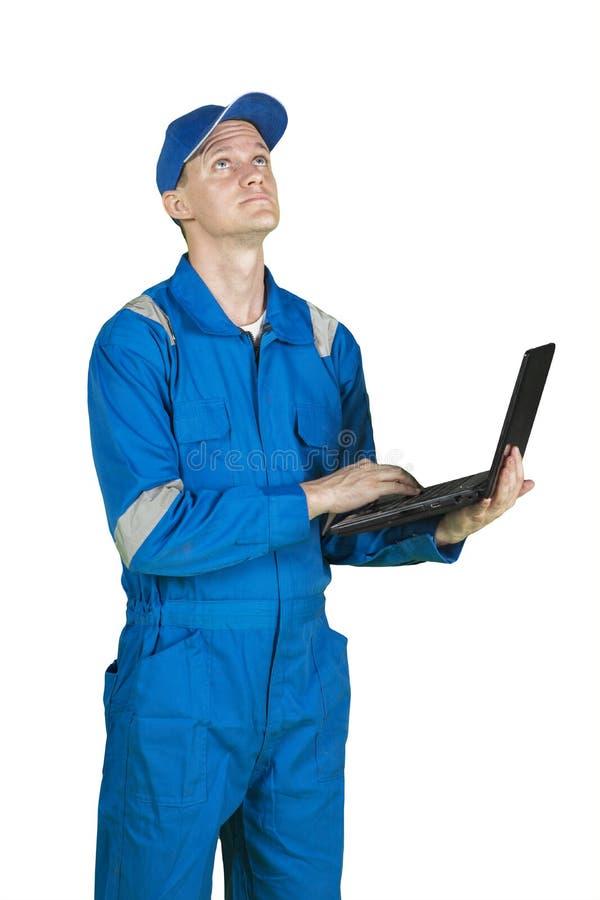 Junger männlicher Mechaniker, der etwas auf Studio denkt stockfotos