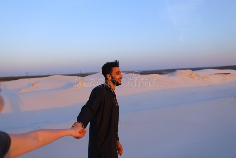 Junger männlicher Moslem führt Mädchen eigenhändig und geht entlang Wüste an s lizenzfreies stockfoto