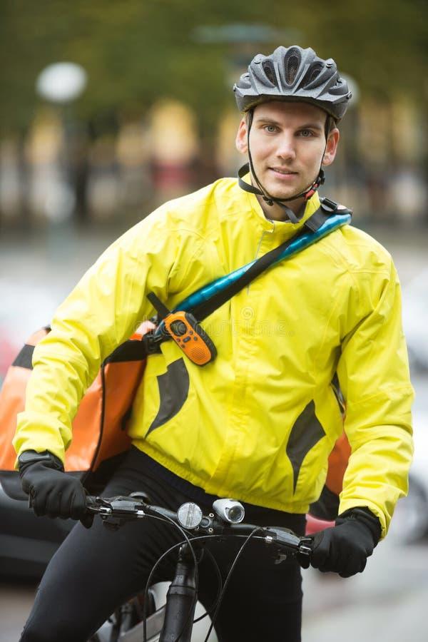 Junger männlicher Radfahrer mit Kurier Delivery Bag On lizenzfreies stockfoto