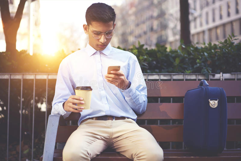 Junger männlicher Reisender, der auf Bank mit Aktenkoffergraseninternet-Website sitzt stockbild