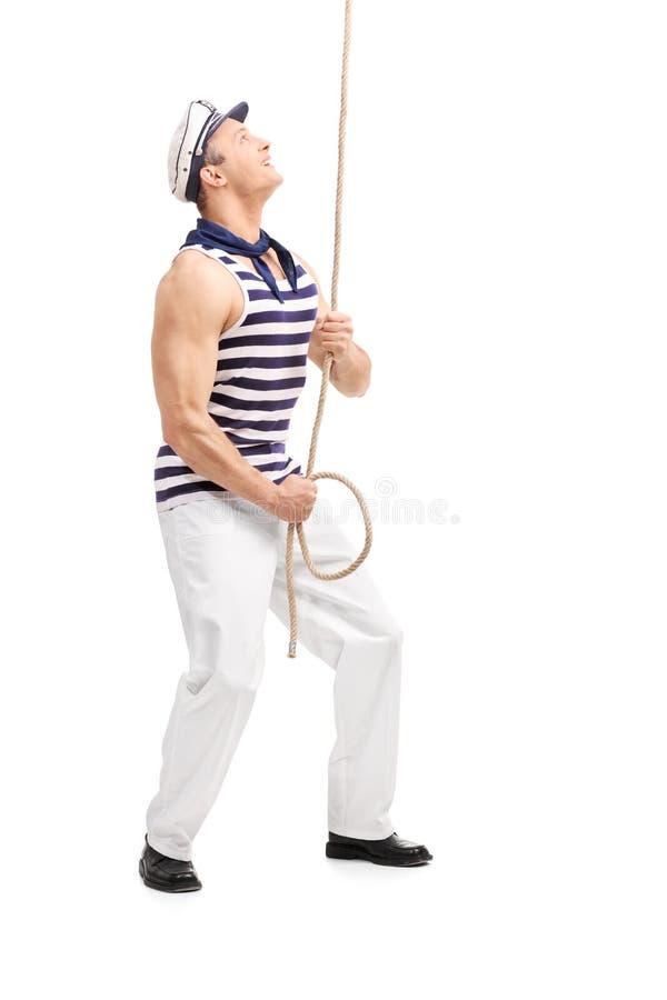 Junger männlicher Seemann, der ein Seil zieht und oben schaut stockfotografie