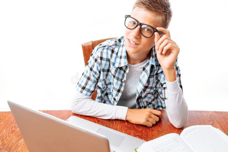 Junger männlicher Student, der Lektionen mit dem Laptop und Büchern bei Tisch sitzen im Studio auf weißem Hintergrund tut lizenzfreies stockbild
