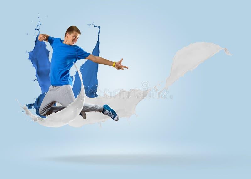 Junger männlicher Tänzer, der mit Spritzen der Farbe springt lizenzfreie stockfotos