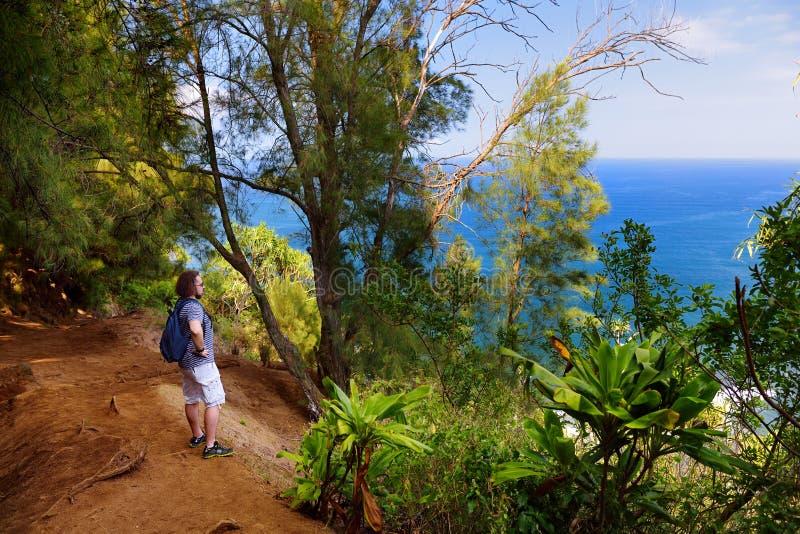 Junger männlicher Tourist, der auf der schönen Pololu-Schleifenspur gelegen nahe Kapaau, Hawaii wandert lizenzfreie stockbilder