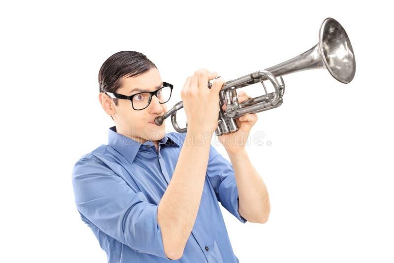 Junger männlicher Trompeter, der die Trompete lokalisiert auf weißem backg spielt stockbilder