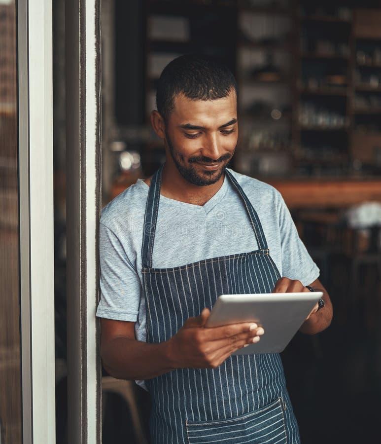 Junger männlicher Unternehmer, der digitale Tablette am Café entranc verwendet lizenzfreies stockfoto