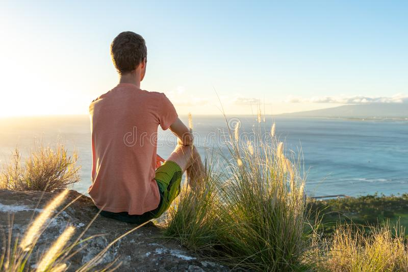 Junger männlicher Wanderer, der auf dem Gipfel von Diamond Head Crater in Honolulu, Oahu, Hawaii, unten schauend zu Waikiki-Stran lizenzfreies stockfoto