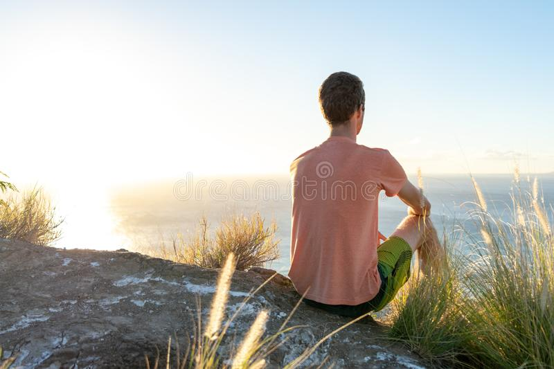 Junger männlicher Wanderer, der auf dem Gipfel von Diamond Head Crater in Honolulu, Oahu, Hawaii, unten schauend zu Waikiki-Stran stockbild
