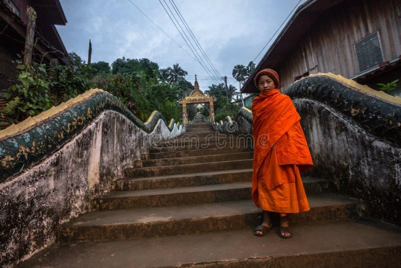 Junger Mönch auf den Schritten, zum von Phousi in Luang Prabang anzubringen stockbilder