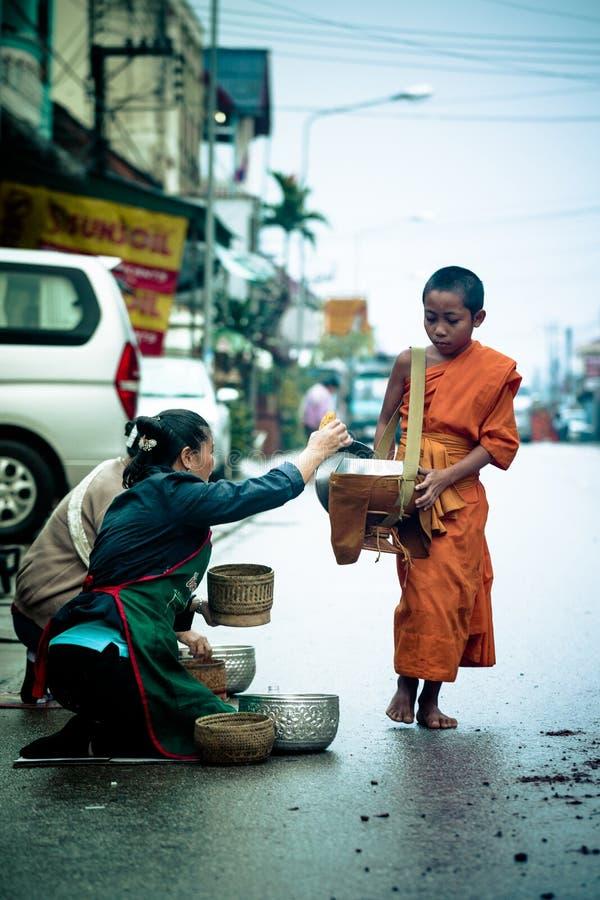 Junger Mönch sammelt Morgenalmosen von den Einheimischen auf der Straße lizenzfreie stockfotos