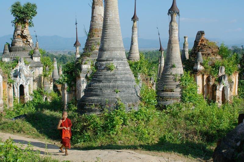 Junger Mönch zwischen stupas lizenzfreie stockfotografie