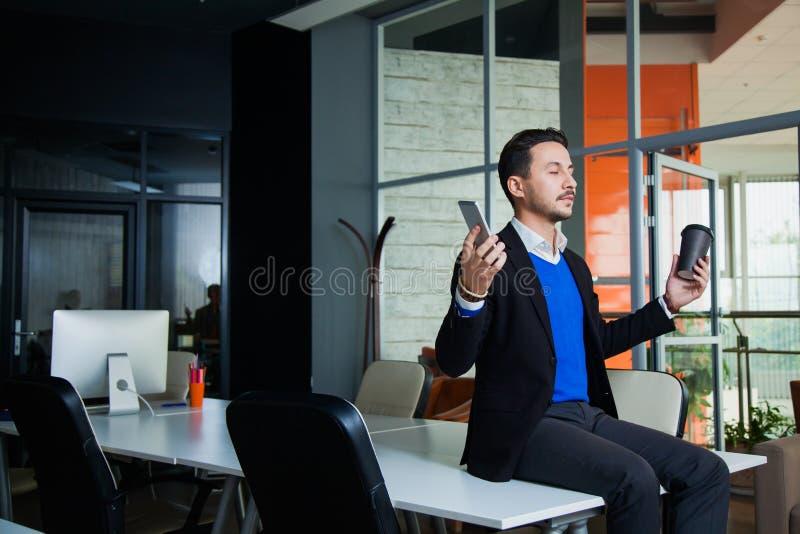 Junger müder Geschäftsmann, der auf Tabelle mit Handy und Kaffee meditiert stockfoto