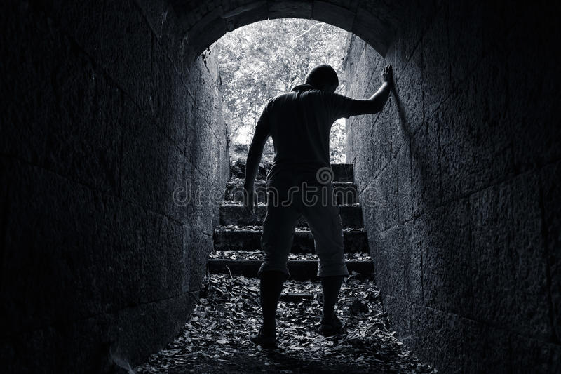 Junger müder Mann lässt dunklen Steintunnel lizenzfreies stockfoto