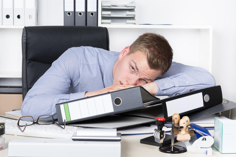 Junger müder Mann liegt auf dem Schreibtisch im Büro stockfotografie