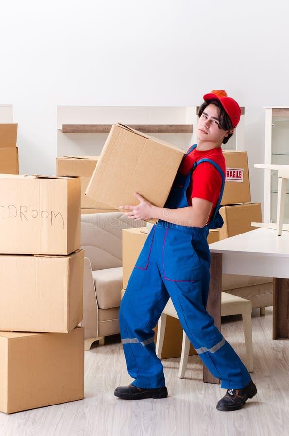 Junger m?nnlicher Auftragnehmer mit den K?sten, die zuhause arbeiten stockfoto