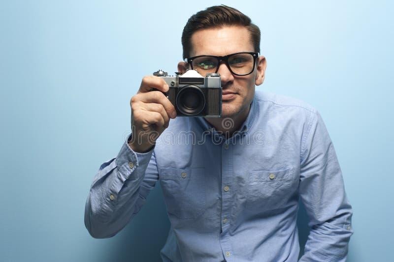 Junger m?nnlicher Fotograf, der eine neue Kamera h?lt stockfotos