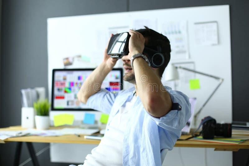Junger m?nnlicher Software-Programmierer, der eine neue APP mit Gl?sern der virtuellen Realit?t 3d im B?ro pr?ft stockbild