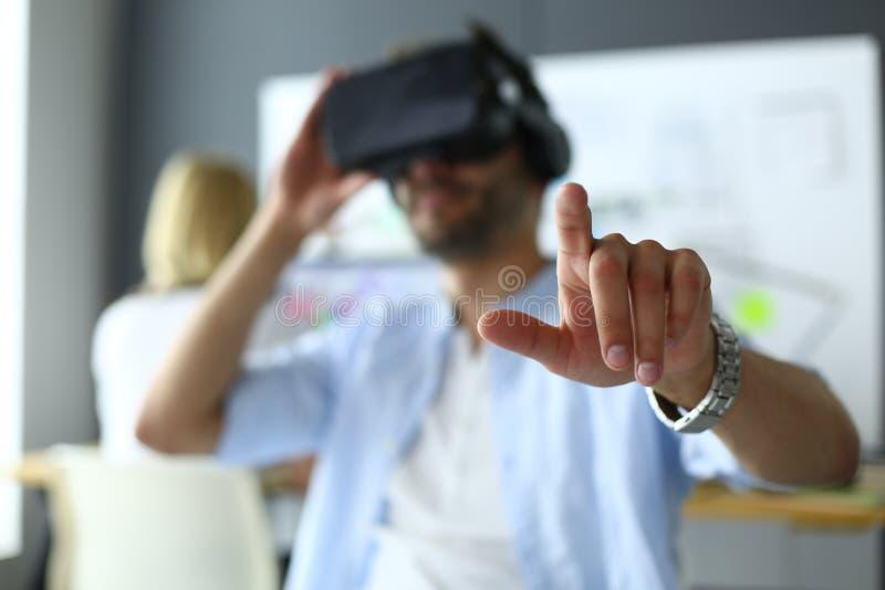 Junger m?nnlicher Software-Programmierer, der eine neue APP mit Gl?sern der virtuellen Realit?t 3d im B?ro pr?ft stockfotos