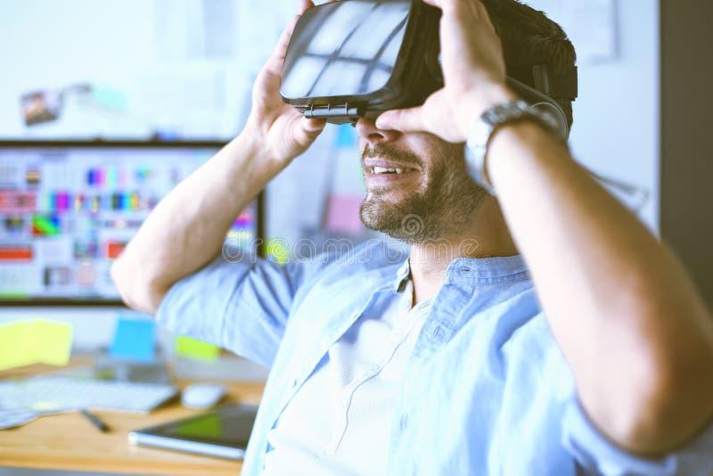 Junger m?nnlicher Software-Programmierer, der eine neue APP mit Gl?sern der virtuellen Realit?t 3d im B?ro pr?ft lizenzfreie stockfotografie