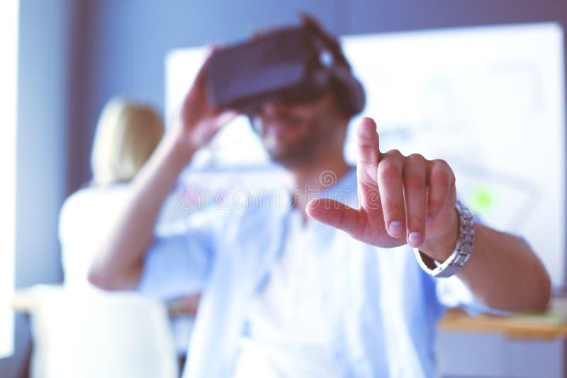 Junger m?nnlicher Software-Programmierer, der eine neue APP mit Gl?sern der virtuellen Realit?t 3d im B?ro pr?ft lizenzfreies stockfoto