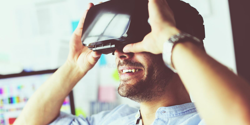Junger m?nnlicher Software-Programmierer, der eine neue APP mit Gl?sern der virtuellen Realit?t 3d im B?ro pr?ft stockfotografie