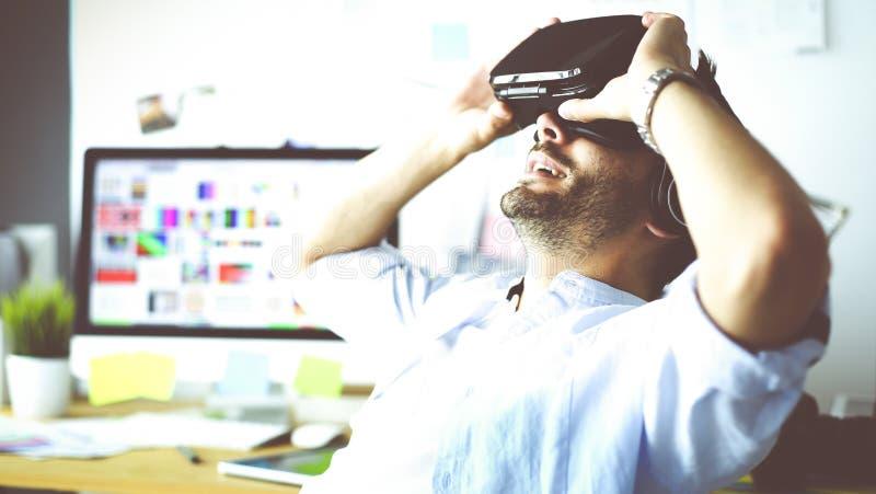 Junger m?nnlicher Software-Programmierer, der eine neue APP mit Gl?sern der virtuellen Realit?t 3d im B?ro pr?ft lizenzfreies stockbild