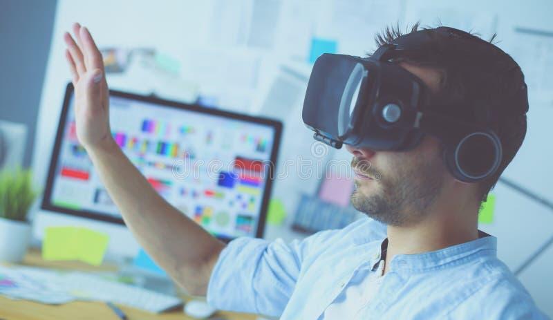 Junger m?nnlicher Software-Programmierer, der eine neue APP mit Gl?sern der virtuellen Realit?t 3d im B?ro pr?ft stockfoto