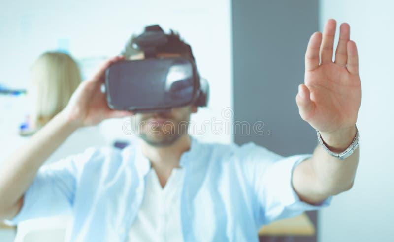Junger m?nnlicher Software-Programmierer, der eine neue APP mit Gl?sern der virtuellen Realit?t 3d im B?ro pr?ft stockbilder
