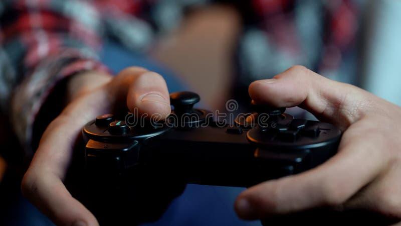 Junger m?nnlicher spielender Computerspiel-Holdingsteuerkn?ppel, s?chtige Person, Freizeit lizenzfreie stockfotografie