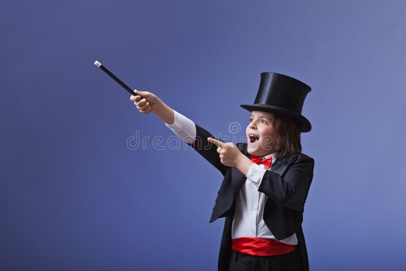 Junger Magier, der mit einem magischen Stab durchführt stockfoto