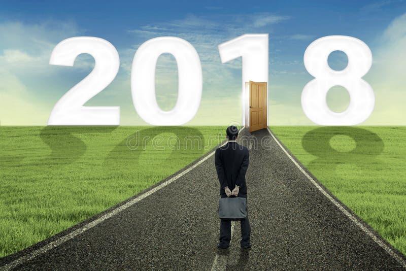 Junger Manager betrachtet Tür und Nr. 2018 lizenzfreies stockbild