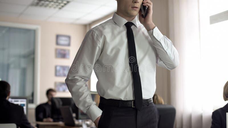 Junger Manager, der am Telefon, seiend ?ber Zeit und Gesch?ftssitz Sitzung spricht einig lizenzfreie stockbilder