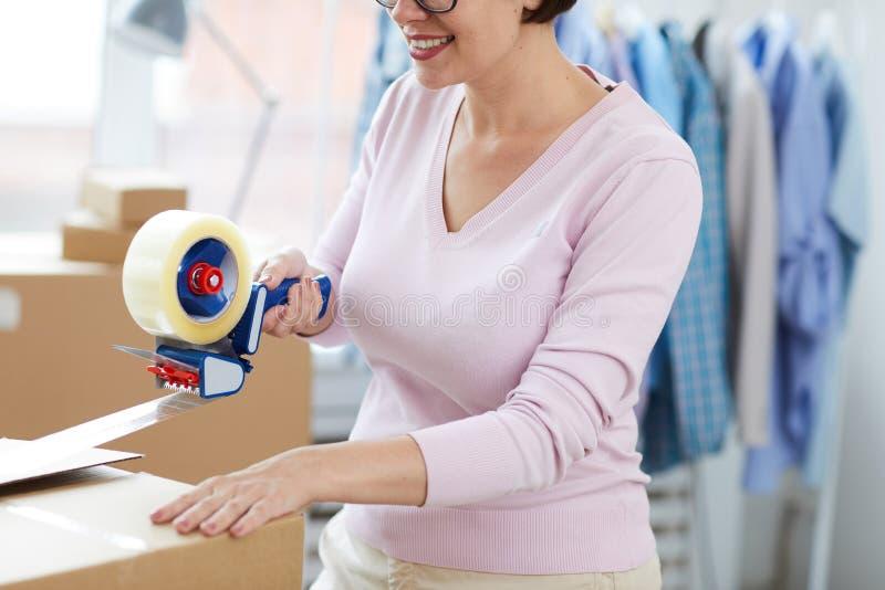 Junger Manager mit der Verpackenpackbandabrollerzufuhr, die einen von Kästen versiegelt stockbild