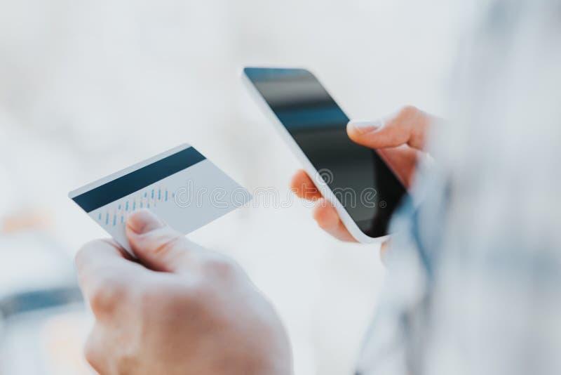 Junger Mann übergibt das Halten der Kreditkarte und die Anwendung des Telefons stockbild