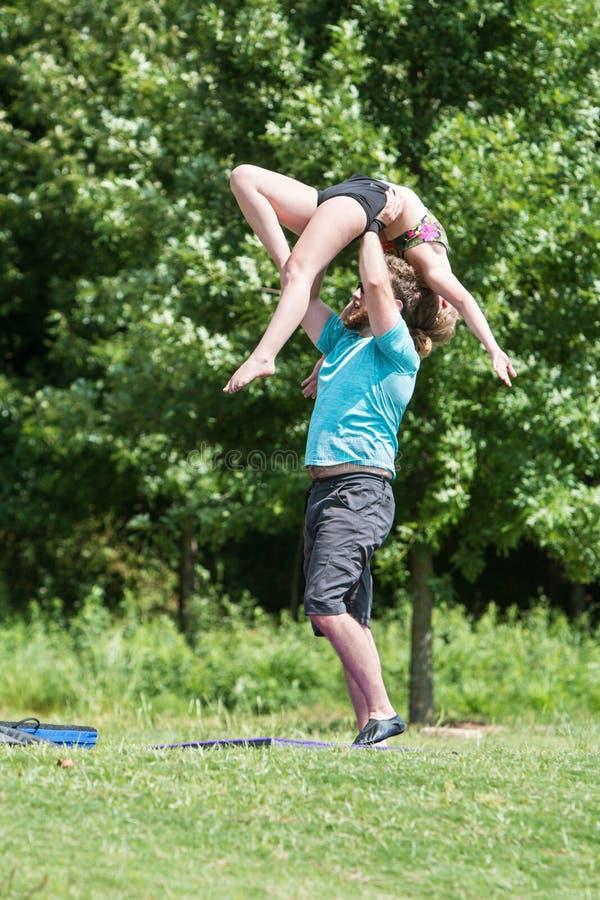 Junger Mann übt, Frau über seinem Kopf im Park anzuheben stockbild