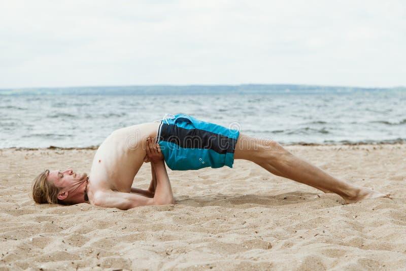 Junger Mann übt Yoga auf dem Strand stockfotografie