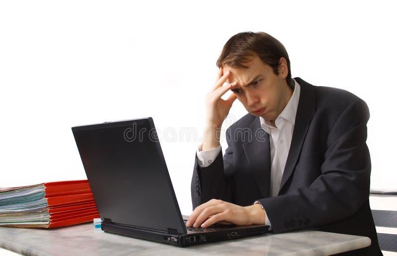 Junger Mann arbeitet an Laptop, nah an Zusammenbruch lizenzfreie stockfotografie