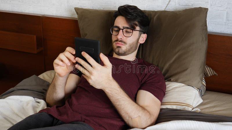 Junger Mann auf Bettlesung mit ebook Leser stockfoto