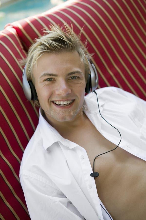 Junger Mann auf deckchair durch Pool hörend Musik auf Kopfhörerporträt stockfoto