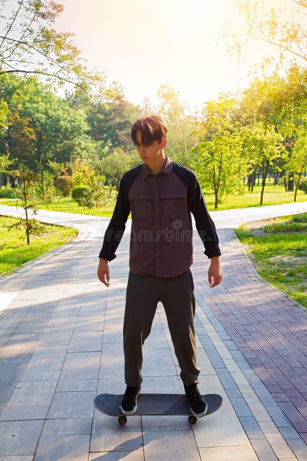 Junger Mann auf dem Skateboard, das fertig wird, in Stadtpark eiszulaufen Jugendlich Jungenschlittschuhläufer lizenzfreie stockfotografie