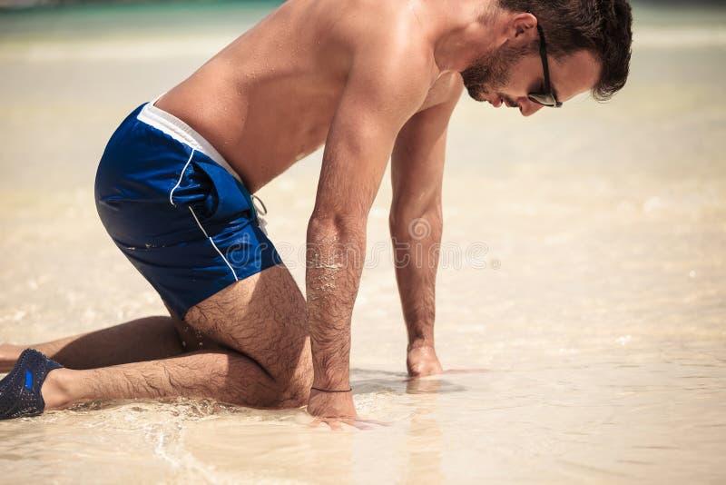 Junger Mann auf dem Strand, auf seinem Knie stockfotos