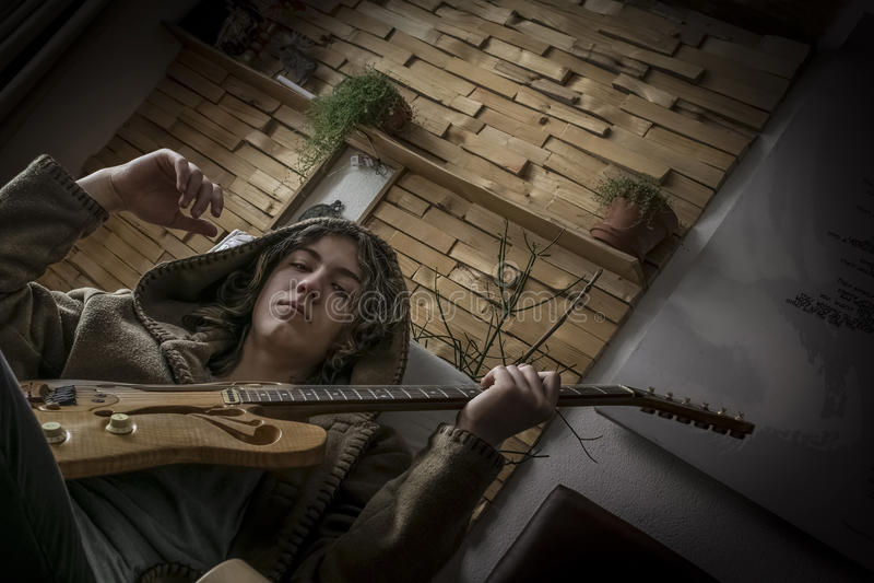 Junger Mann auf einem Stuhl mit handgemachter Gitarre stockfotografie