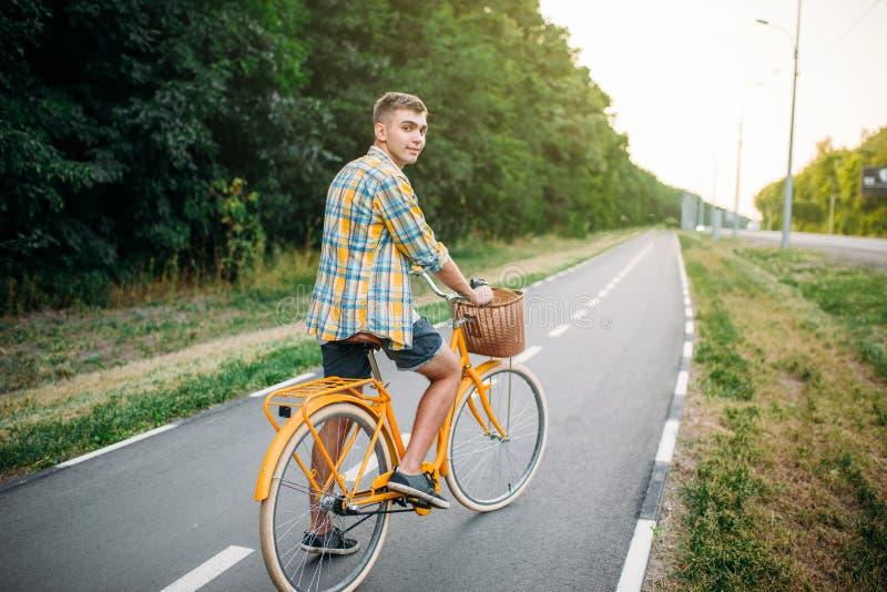 Junger Mann auf gelbem Weinlesefahrrad mit Korb stockbild