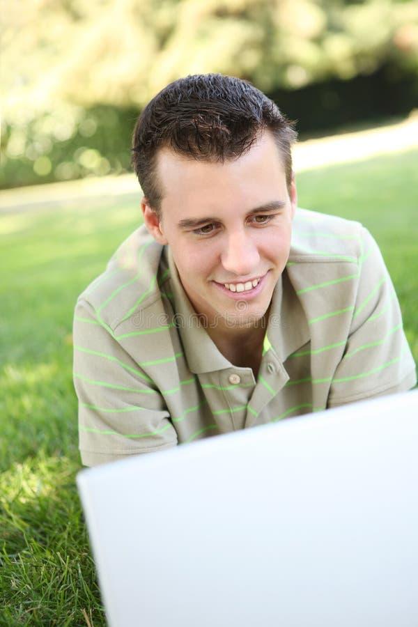 Junger Mann auf Laptop im Park stockfotos