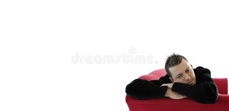 Junger Mann auf rotem Sofa stockbilder