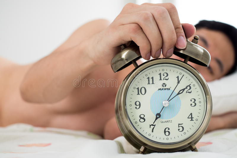 Junger Mann auf seinem Kopfende, wissend, dass er und spät verschlief lizenzfreie stockbilder