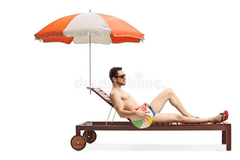 Junger Mann auf sunbed mit einem Regenschirm, der einen aufblasbaren Ball hält stockbilder